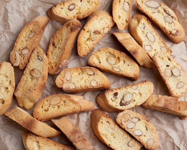 Kawałki pieczonych włoskich ciastek biscotti na brązowym zmiętym papierze
