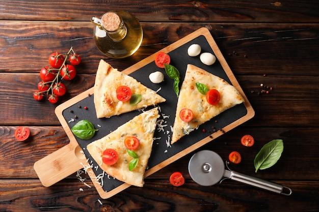 Kawałki pizza i składniki na drewnianym tle