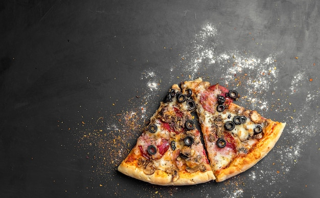 Kawałki pizzy na ciemnej czarnej desce, tradycyjna włoska pizza