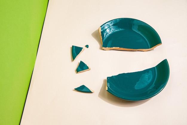 Kawałki potłuczonego talerza na stole w studio