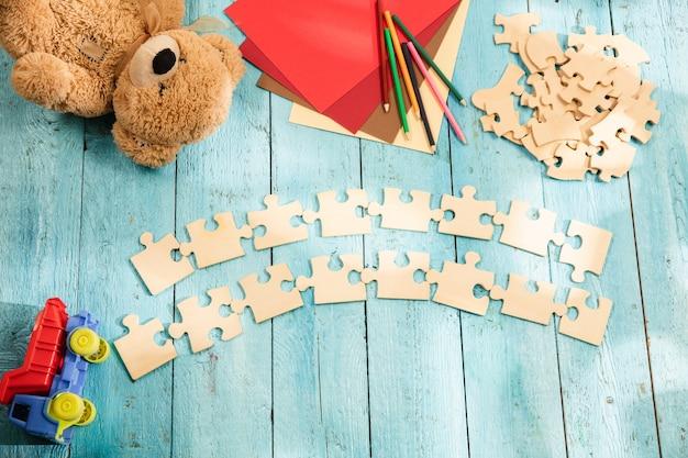 Kawałki puzzli na powierzchni drewnianego stołu z zabawkami i kolorami