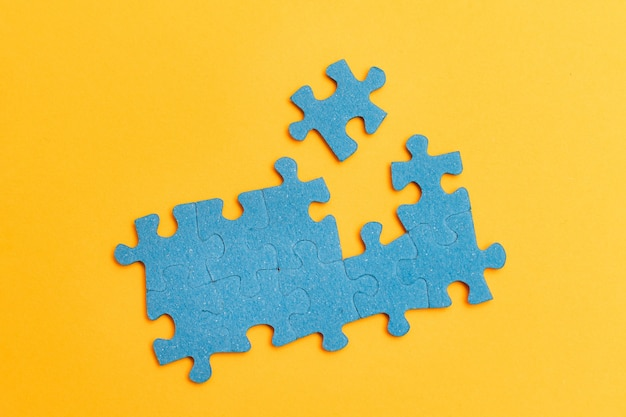 Kawałki puzzli na żółtym tle