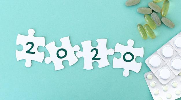 Kawałki puzzli w rzędzie do pisania obok tabletek i fonendoskopu