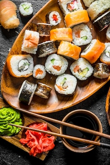 Kawałki pysznego sushi, bułki i maki. na powierzchni rustykalnej