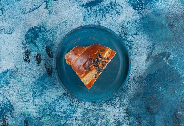 Kawałki rogalika z czekoladą na drewnianym talerzu, na marmurowym stole.