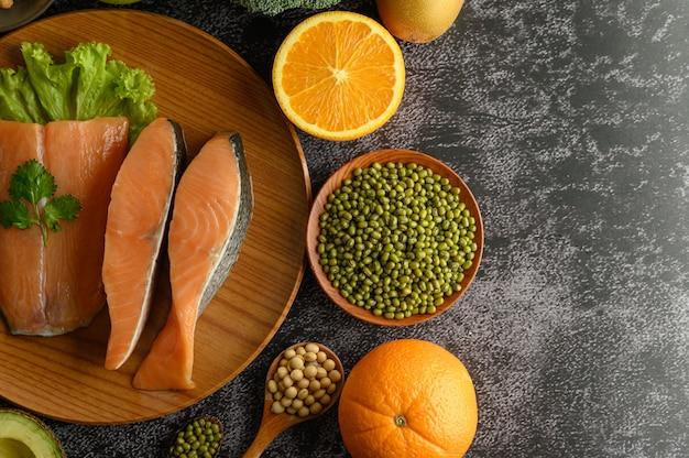 Kawałki roślin strączkowych, owoców i łososia na drewnianym talerzu.