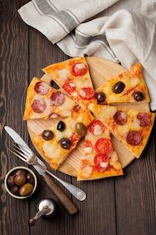 Kawałki różnych greckich pizz z oliwkami, włoską margaritą i pepperoni na ciemnym drewnianym rustykalnym stylu.