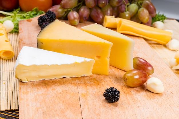 Kawałki różnych serów na desce serów ze świeżymi winogronami, jeżynami i oliwkami na smaczny bufet