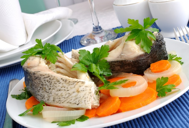 Kawałki ryby gotowane z marchewką i cebulą z bliska