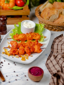 Kawałki sash kebab z piersi kurczaka, grillowane i podawane z sosem śmietanowym, sumakiem i sałatą