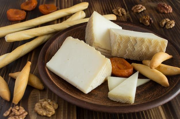 Kawałki sera i paluszki chlebowe na brązowym talerzu