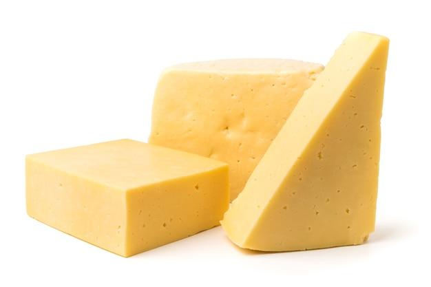 Kawałki sera o różnych kształtach na białym tle