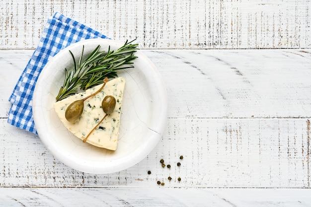 Kawałki sera pleśniowego lub sera brie w misce z rozmarynem, kaparami i pieprzem.