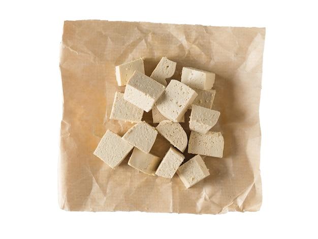 Kawałki sera tofu na papierze na białym tle. przystawka z grillowanego sera. leżał na płasko.