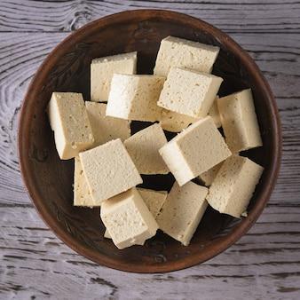 Kawałki sera tofu w glinianym talerzu na drewnianym. ser sojowy. produkt wegetariański. leżał na płasko.