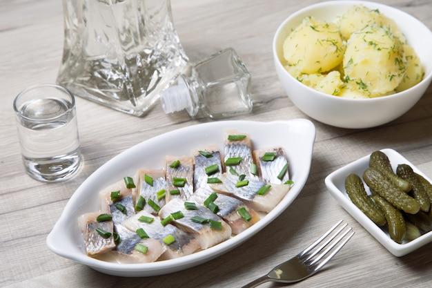 Kawałki śledzia z cebulą, korniszonami, gotowanymi ziemniakami i wódką. selektywne ustawianie ostrości