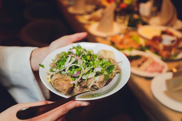 Kawałki smażonego mięsa z cebulą i jęczmieniem na białym talerzu obok sałaty.