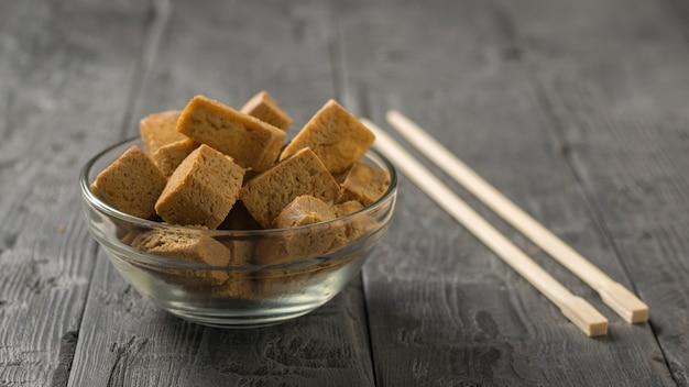 Kawałki smażonego sera tofu w szklanej misce na drewnianym stole. przystawka z grillowanego sera.
