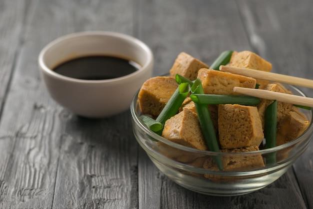 Kawałki smażonego sera tofu w szklanej misce z zieloną cebulą na drewnianym stole. przystawka z grillowanego sera.