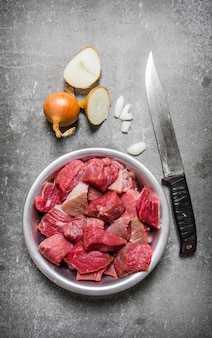Kawałki surowego mięsa w misce z nożem do siekania i cebulą na kamiennym stole