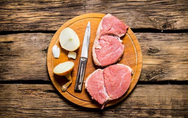 Kawałki surowego mięsa z cebulą na desce do krojenia. na drewnianym stole. widok z góry