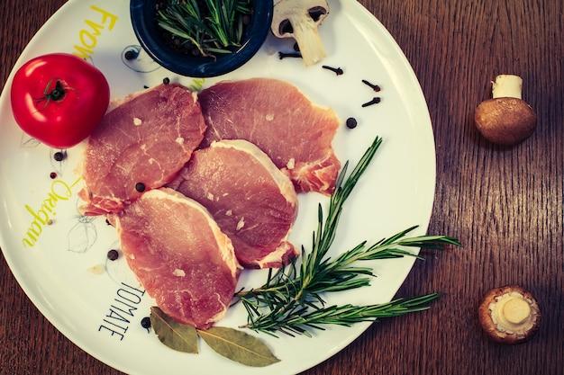 Kawałki surowego steku wieprzowego z przyprawami i ziołami rozmarynem, pieczarkami, pomidorem, solą i pieprzem na białym talerzu, widok z góry