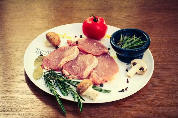 Kawałki surowego steku wieprzowego z przyprawami i ziołami rozmarynem, pieczarkami, pomidorem, solą i pieprzem na białym talerzu
