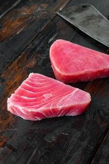 Kawałki surowego tuńczyka i stary tasak rzeźniczy na starym ciemnym drewnianym stole