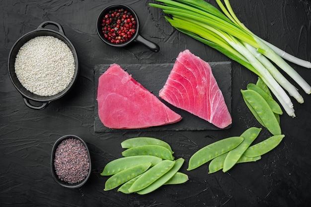 Kawałki surowego tuńczyka ze składnikami groszek, sezam i zioła, osadzone na kamiennej desce, na czarnym kamieniu