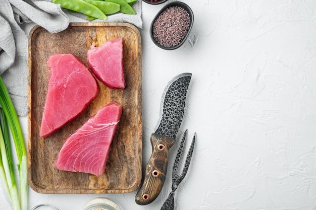 Kawałki surowego tuńczyka ze składnikami groszek, sezam i zioła ustawione na drewnianej tacy, na białym kamieniu