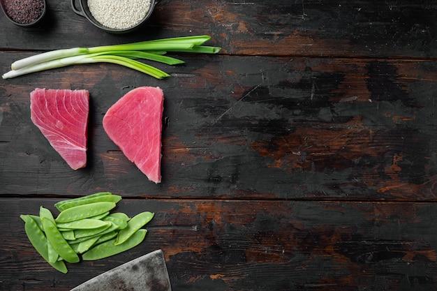 Kawałki surowego tuńczyka ze składnikami groszek, sezam i zioła ustawione na starym ciemnym drewnianym stole