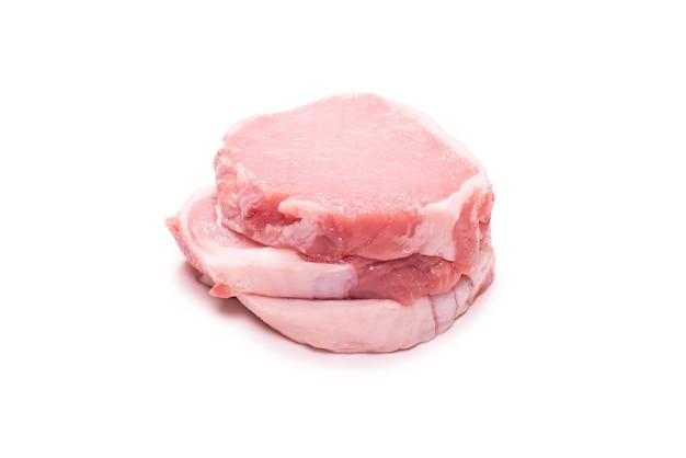 Kawałki surowej wieprzowiny na białym tle na białej powierzchni. widok z góry.