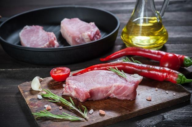 Kawałki surowej wieprzowiny na desce do krojenia, gotowe do pieczenia. przyprawy i olej