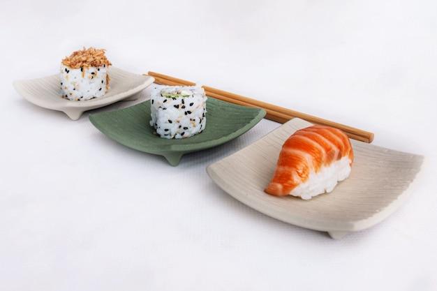 Kawałki sushi w kwadratowych talerzach w neutralnym kolorze z pałeczkami.