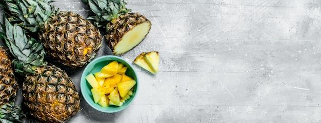 Kawałki świeżego ananasa w misce i dojrzałe ananasy. na białym tle rustykalnym