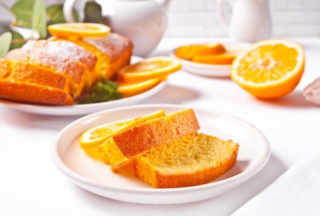 Kawałki świeżego domowego pieczonego ciasta cytrynowego w plasterkach na białym talerzu.