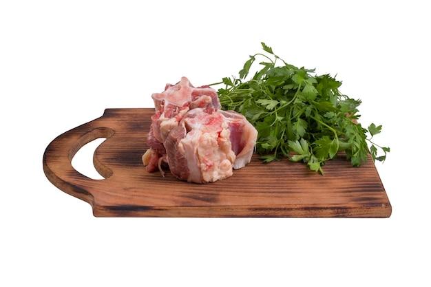 Kawałki świeżego surowego mięsa wołowego wołowego na drewnianej desce na białym tle