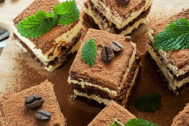 Kawałki tiramisu z ziarnami kawy i listkami mięty