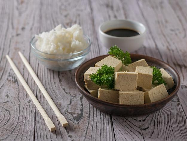 Kawałki tofu, ryżu, sosu sojowego i pałeczek na drewnianym stole. ser sojowy. produkt wegetariański.