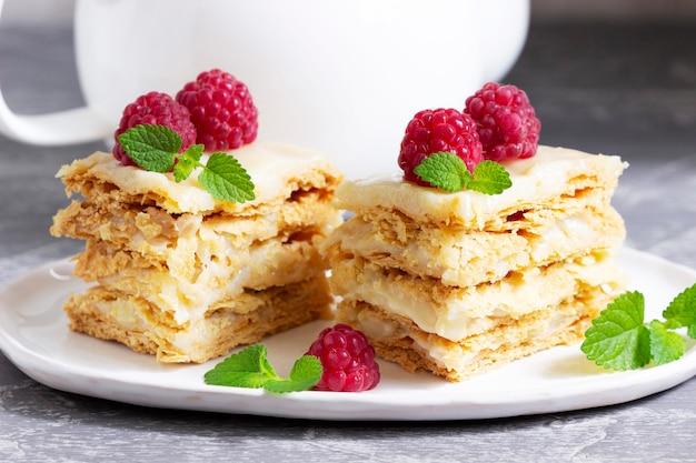 Kawałki tortu napoleońskiego ozdobione malinami i liśćmi melisy na jasnym tle. selektywne skupienie.