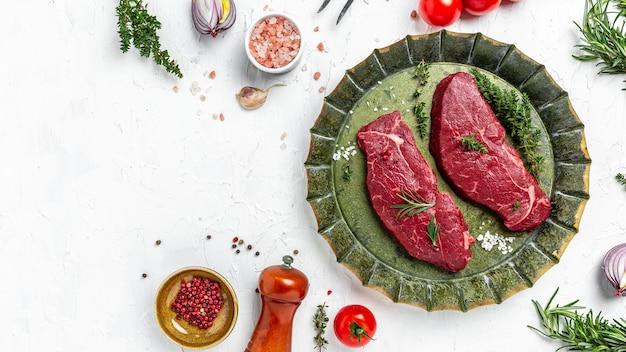 Kawałki ugotowanego rumsztyku z przyprawami podawane na starej tacy mięsnej. stek z marmurkowej wołowiny czarnego angusa. stek z rampy surowej wołowiny, widok z góry.