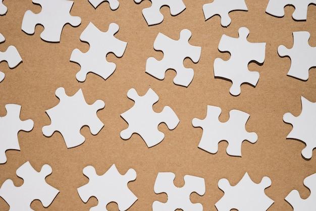 Kawałki układanki na brązowym papierze teksturowanej tło