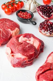 Kawałki wołowiny chuck eye roll, górne ostrze, rumsztyk z czerwonym winem w kieliszku i butelce, zioła i granat. mięso ekologiczne. białe tło z teksturą. widok z boku w pionie.