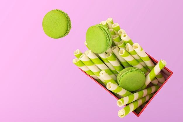 Kawałki zielonych makaroników pistacjowych lub francuskich makaroników spadające na czerwone pudełko upominkowe