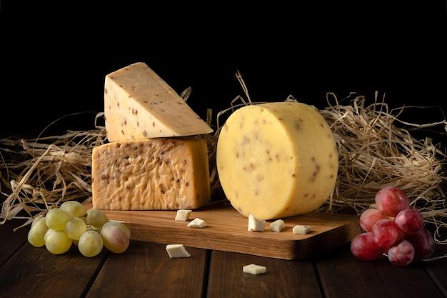 Kawałki żółtego twardego sera ziarnistego z orzechami i pestkami słonecznika, siano, gałązki czerwonych i zielonych winogron na desce do krojenia w widoku z boku