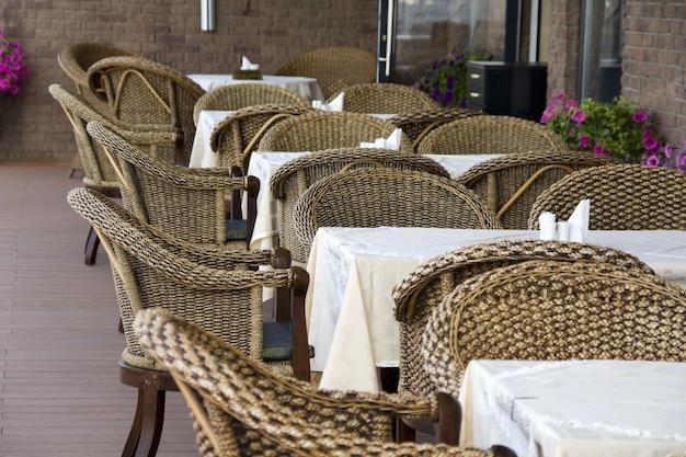 Kawiarenka na dworze. rząd rattanowych krzeseł i stołów