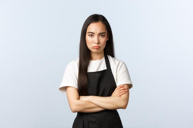 Kawiarnia, mały biznes i koncepcja uruchamiania. ponura obrażona urocza azjatycka pracownica w kawiarni, barista lub kelnerka pracująca w restauracji, stoi zamknięta poza ze skrzyżowanymi rękami, dąsa się, jest na ciebie wściekła