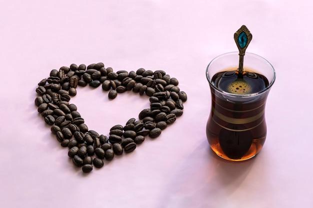 Kawiarnie i restauracje. kubek orzeźwiającej, czarnej kawy w kształcie serca i ziaren kawy. miejsce na napis. koncepcja gorących napojów i miłości.