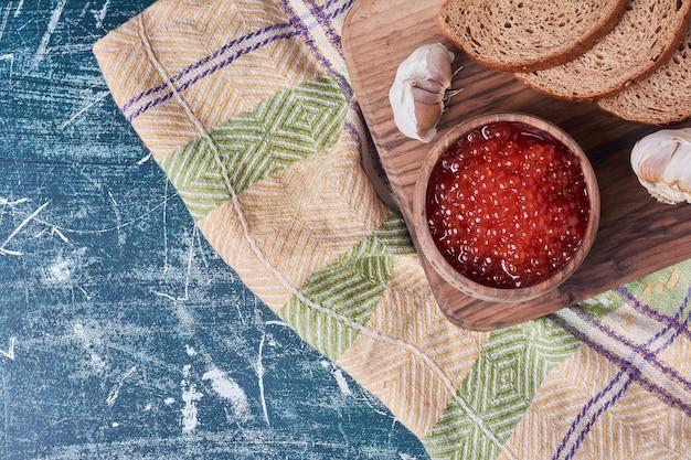 Kawior czerwony z kromkami chleba.