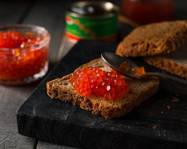 Kawior z łososia na chlebie żytnim na ciemnym drewnianym stole rustykalnym